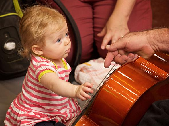 Toddler reaches out and touches Cello.